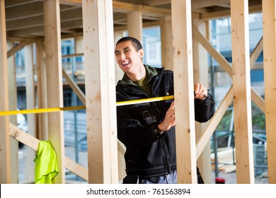 Carpenter Laughing While Measuring Wood At Construction Site