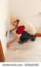 carpenter laying parquet floor in a single family home