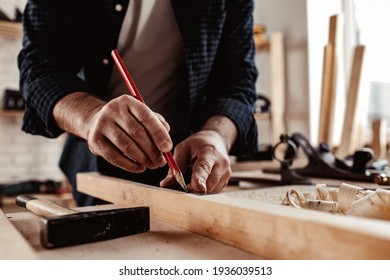 Carpenter makes pencil marks on a wood plank