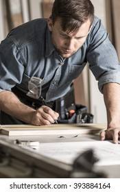 Carpenter is making a sketch of new furniture