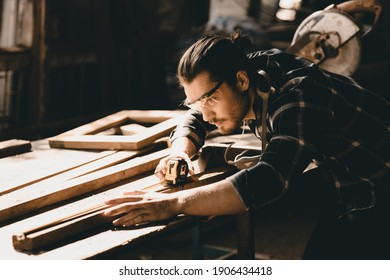 Carpenter man attend to making masterpiece woodworks handcrafted furniture fine measure in wood workshop.