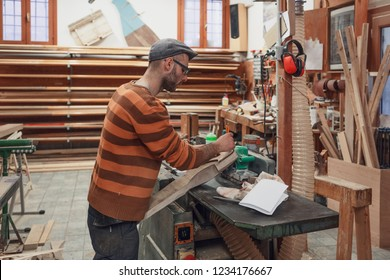 Carpenter man in brown sweater marking wooden detail using pencil, standing at the crafting table in workshop