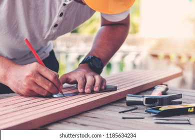 Carpenter man  measuring and writing on wood in carpentry shop.Labor market of joiner and craftsman concept.