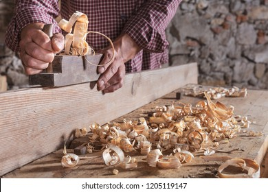 Carpenter man scraping curled wood scraps with hand plane tool and wooden plank. Blurry stone wall in background.
