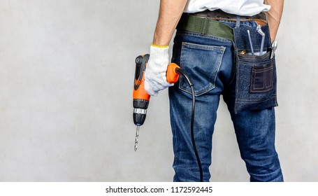 Carpenter man stand in carpentry shop with concrete background and holding drill on hand.Labor market of joiner and craftsman concept.Free space.