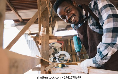 Carpenter man using drilling tool for wood of his own housing at work site. Carpenter makes facade details for construction. housekeeping maintenance concept.