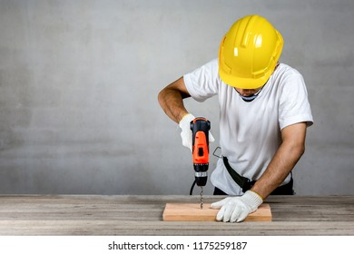 Carpenter man wear safety helmet drilling a wood in carpentry shop.Labor market of joiner and craftsman concept.Free space.
