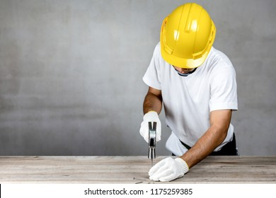 Carpenter man wear safety helmet hammering a nail in carpentry shop.Labor market of joiner and craftsman concept.Free space.