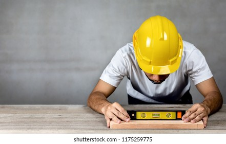 Carpenter man wear safety helmet measuring  wood with building level in carpentry shop.Labor market of joiner and craftsman concept.Free space.
