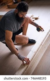 Carpenter measuring boards in a room with loft interior.
