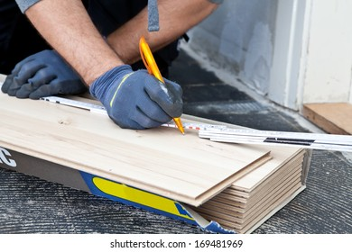 Carpenter measuring new wooden flooring planks using a builders ruler during construction or renovation of a building, close up view of his hands