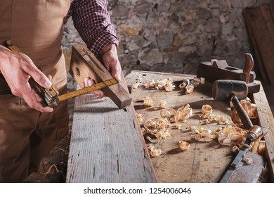 Carpenter measuring wood with bent ruler while it sits on workbench and stone wall in background behind plank floor