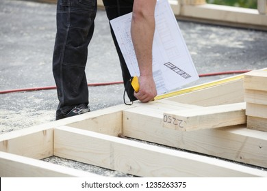 "Carpenter measuring wooden 2x4"" wall structure, checking the building plan at the building site. Building industry, carpentry concept."