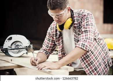 Carpenter measuring a wooden plank