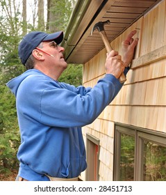 Carpenter nailing cedar shingles to exterior wall