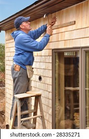 Carpenter nailing cedar shingles to house