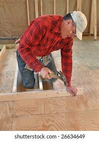 Carpenter nailing interior wall together