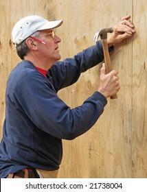 Carpenter nailing plywood sheathing into place
