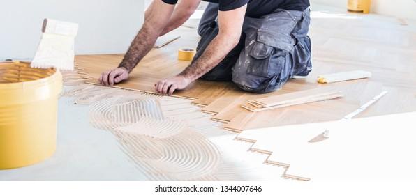 Carpenter on work putting wood parquet pieces. Home construction