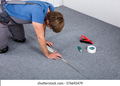 Carpenter In Overall Crouching Laying Carpet On Floor At Home