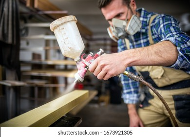 Carpenter with paint spray gun painting wooden plank in carpentry workshop
