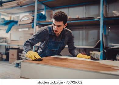 Carpenter is painting a wood with lacquer. The joiner covers the furniture with varnish in the production workshop of carpentry perspective view