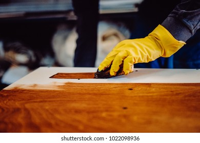 Carpenter is painting a wood with lacquer. Toned image. The joiner covers the furniture with varnish in the production workshop of carpentry. close up view