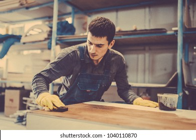 Carpenter is painting a wood with lacquer. Toned image. The joiner covers the furniture with varnish in the production workshop of carpentry.