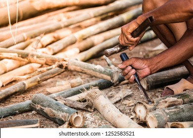 The carpenter is perforating the bamboo to make furniture.