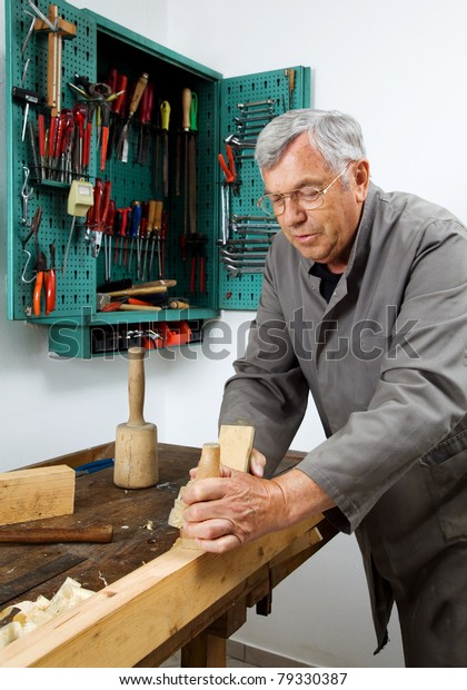 A carpenter with a planer and wood shavings in the workshop.