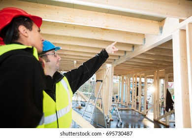Carpenter Pointing On Roof Beam While Standing By Colleague