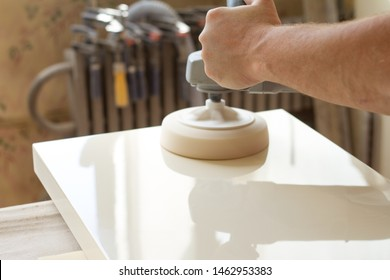 A carpenter polishes the surface of the facade before assembling furniture on a blurred background carpentry workshop, selective focus
