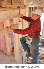 Carpenter pounding a nail into an interior partition