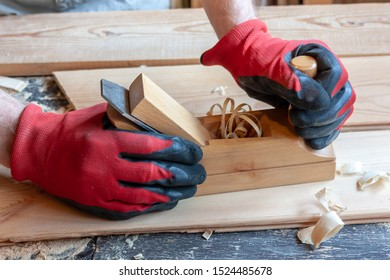 A carpenter in red cloth gloves holds a wooden jointer in his hands close-up. Sawdust, shavings, boards on the table