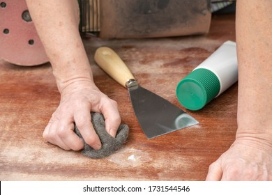Carpenter repairs a defect in the wood with filler putty