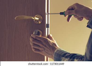 Carpenter repairs the locksmith, sets the door lock on the wooden door.