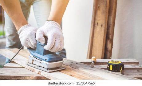 Carpenter sanding with electric sander polisher.