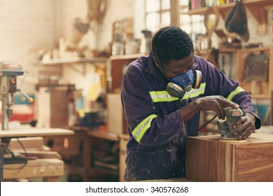 A carpenter sanding a plank in his workshop