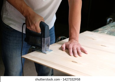 Carpenter is sawing a plywood sheet with electric jig saw machine in carpentry workshop. Close up hand with jigsaw. Carpentry concept.