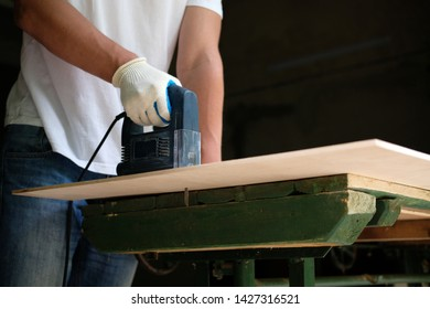 Carpenter is sawing a plywood sheet with jig saw machine in carpentry workshop. Side view. DIY concept.