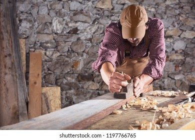 Carpenter smoothing out long wooden beam on top of table with hand plane and other planks in front of stone wall