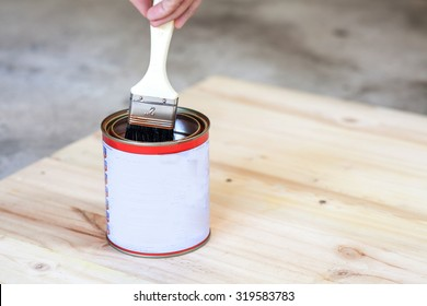 Carpenter is soaking his brush into the can of paint.
