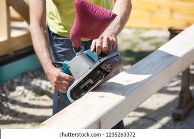 Carpenter softening edges on construction beams with electric belt sander. DIY and carpentry industry concept.