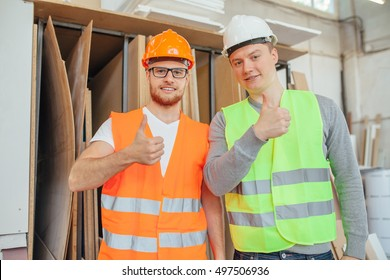 A carpenter is standing in carpentry shop wearing safety uniform