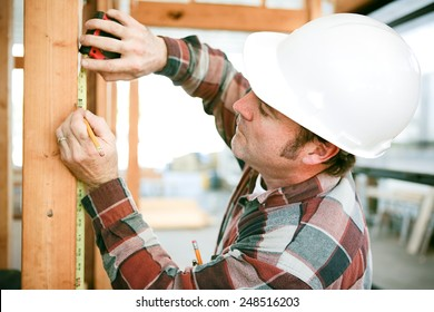 Carpenter taking measurements on a construction site.