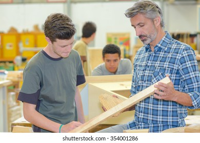 Carpenter talking to apprentice