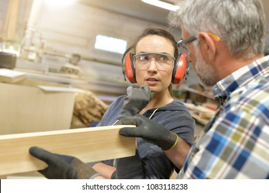 Carpenter teaching apprentice how to cut wood