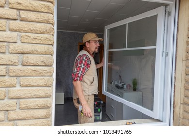 carpenter testing a replaced window after installation