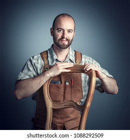 carpenter with unfinished chair, studio shot portrait