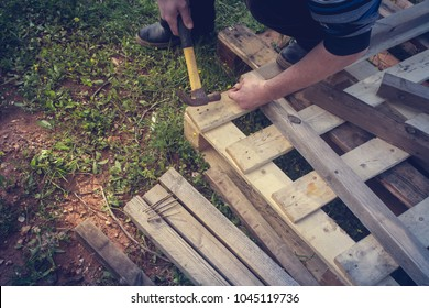 A carpenter is upcycling a wooden pallet making a construction with a hammer